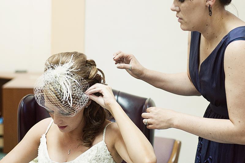 bride adjusting her birdcage veil