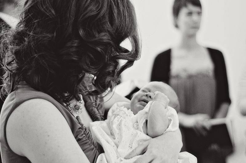 mom holding baby in christening gown