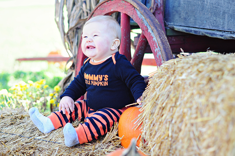 laughing baby sitting on a wagon